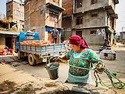 01 MARCH 2017 - BUNGAMATI, NEPAL: A woman draws water from a well while workers deliver bricks to a site to rebuild homes destroyed in the 2015 earthquake. Recovery seems to have barely begun nearly two years after the earthquake of 25 April 2015 that devastated Nepal. In some villages in the Kathmandu valley workers are working by hand to remove ruble and dig out destroyed buildings. About 9,000 people were killed and another 22,000 injured by the earthquake. The epicenter of the earthquake was east of the Gorka district.     PHOTO BY JACK KURTZ