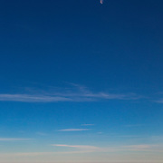 The half moon is visible over the summit of Mount Rainier, which pokes out from a thick cloud bank in Washington state. Mount Rainier, with an elevation of 14,411 feet (4,392 meters), is the tallest mountain in Washington and the highest volcano in the Cascade Range.