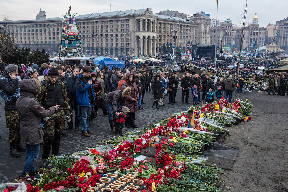 KIEV, UKRAINE - FEBRUARY 23: People visit a memorial to anti-government protesters killed in chashes with police on Independence Square on February 23, 2014 in Kiev, Ukraine. After a chaotic and violent week, Viktor Yanukovych has been ousted as President as the Ukrainian parliament moves forward with scheduling new elections and establishing a caretaker government. (Photo by Brendan Hoffman/Getty Images) *** Local Caption ***