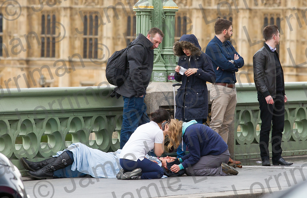 Terrorist incident on Westminster Bridge, London<br /> <br /> Pictured: Medics and passers by treat a victim on Westminster Bridge, London<br /> <br /> Jamie Lorriman<br /> mail@jamielorriman.co.uk<br /> www.jamielorriman.co.uk<br /> 07718 900288