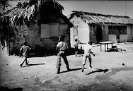 Children born of Haitian descent play among disheveled waddle and daub houses in Batey 2, a group housing area. These children are often denied citizenship within the country, which creates difficulties in obtaining access to health care and continued education..