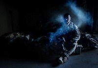 Before going on patrol, a U.S. Army soldier smokes a cigarette on his cot at a remote combat outpost in Buhriz, Iraq, on Feb. 15, 2007.