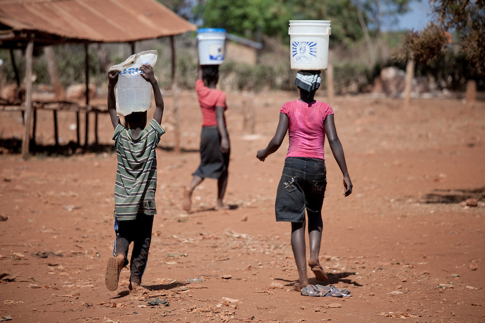 Three kids carry water in buckets and bags on their head on Ile de La Gonave, Haiti