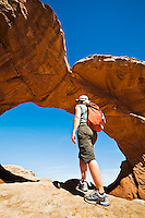 A woman walking up to Broken Arch in Arches National Park, Utah, USA.