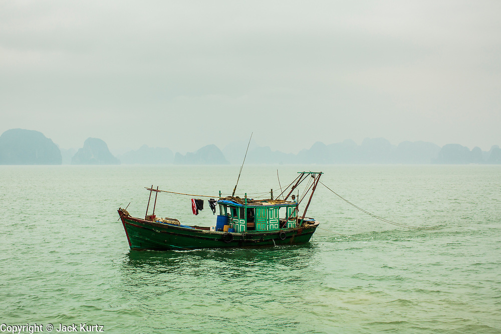 03 APRIL 2012 - HA LONG, VIETNAM: A Vietnamese fishing trawler in Ha Long Bay. In 1994 UNESCO declared 174 square miles of Ha Long Bay a World Heritage Site. There are nearly 2000 distinct rock islands in the bay, which for centuries has been the home to isolated fishing villages. Now thousands of tourists stream through the bay and around the islands every day on cruise ships. On the Vietnamese mainland, around the town of Ha Long, real estate companies are developing exclusive condominium and apartment complexes for use as weekend homes for people in Hanoi, about a 3.5 hour drive from Ha Long.    PHOTO BY JACK KURTZ