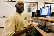 """Woodbourne Correctional Facility inmate and Bard College student Abdullah Kamau Sankofa studies in the computer room. He has been sentenced to 18 years in prison at the age of 17. He graduated from Bard College with fellow inmate Carlos Rosario in May 2010. (Book: The Coming of the French Revolution)..Story: The Bard Prison Initiative.Former inmate Carlos Rosario, 35-year-old husband and father of four, was released from Woodbourne Correctional Facility after serving more than 12 years for armed robbery. Rosado is one of the students participating in the Bard Prison Initiative, a privately-funded program that offers inmates at five New York State prisons the opportunity to work toward a college degree from Bard College. The program, which is the brainchild of alumnus Max Kenner, is competitive, accepting only 15 new students at each facility every other year. .Carlos Rosario received the Bachelor of Arts degree in social studies from the prestigious College Saturday, just a few days after his release. He had been working on it for the last six years. His senior thesis was titled """"The Diet of Punishment: Prison Food and Penal Practice in the Post-Rehabilitative Era,"""".Rosado is credited with developing a garden in one of the few green spaces inside the otherwise cement-heavy prison. In the two years since the garden's foundation, it has provided some of the only access the prison's 800 inmates have to fresh vegetables and fruit...Rosario now works for a recycling company in Poughkeepsie, N.Y...Photo © Stefan Falke"""