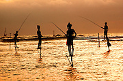 SRI LANKA, SEA COASTS fishermen fishing from perches on stilts above the breaking surf along the islands' southern coast