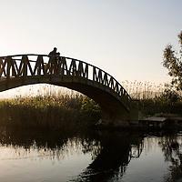 A couple walk their dog along an inlet bridge in the Aegean seaside town of Gokova, Turkey April, 2013