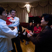 BEIJING, 25. JANUARY, 2009 :   Mr. Li, a paper factory owner, talks to a relative while taking care of his grandchild on new years' eve.  <br /> Mr. Li, a paper factory owner, is facing one of his most difficult times .&quot; Last November the market suddenly went down ,&quot; Li says.   <br /> He had bought paper, a lot of paper, and paid 7000 Yuan/ t .<br />  Li's company buys paper from paper mills and lives from the sales to publishing houses and other companies.  Since the market's collapse , he manages to sell the paper only for 6000 Yuan/t.<br /> His clients' export business to the USA had shrunk in Southern China. Mobile phone manufacturers don't need paper for the instruction guides to their mobile phones anymore as their US clients buys less China- made mobile phones.<br />  Toy manufacturers don't need paper anymore  because Americans import less toys from China. &quot; The crisis has driven many of my clients into bancruptsy&quot;, says Li.<br />  <br /> China's Communist Party  which will celebrate its 60th anniversary in October, currently faces its biggest challenge since the beginning of the economic reforms 30 years ago  : &quot; The phase of  rapid economic growth is over. For the first time the government is threatened with a  mistrust of a wide section of the population&quot;, warns the Communist party's Shang Dewen in Beijing.   <br /> Not only the China's poorest worry about the furture, but as well China's middle class is concerned about the crisis.     1,5 Millionen university graduates didn't find a job until the end of 2008  and this summer there'll be an additional  6,1 Million new graduates. More than 12 percent of university graduates face unemployment in 2009.
