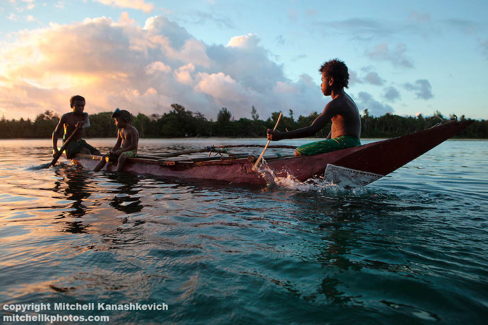 Ni Vanuatu boys sit in an outrigger canoe in the lagoon which separates Rah from Mota Lava Island, Banks Island group, Torba Province, Vanuatu