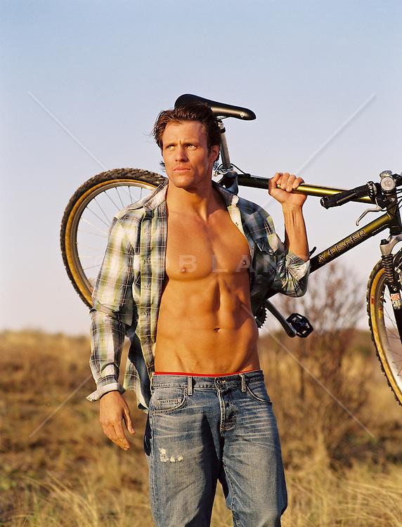 cdn.c.photoshelter.com/img-get2/I00004ki5rqEjilo/fit=1000x750/man-with-an-open-shirt-carrying-a-bicycle-on-his-shoulder.jpg