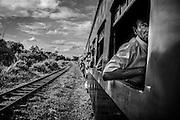 A man rides on the Yangon Circular Railway, an open air train that circumnavigates the captital city and it's rural suburbs.