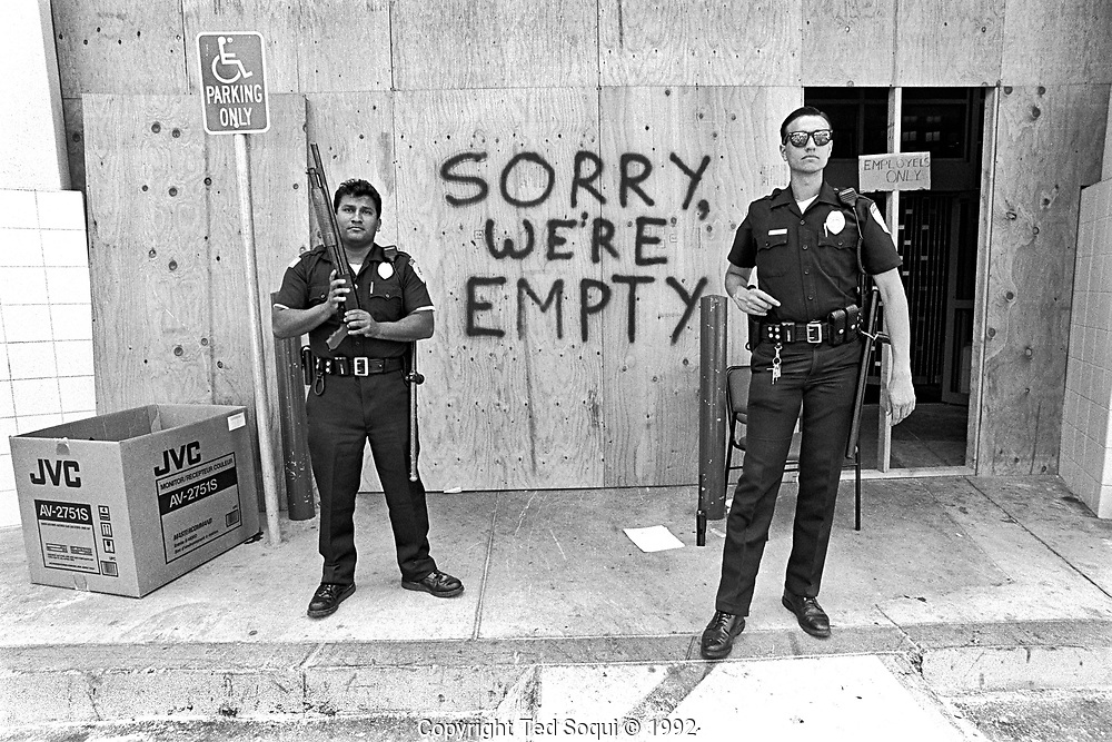 Two armed officers stand guard out front of an electronics store on Sunset Blvd. and La Brea after being looted by rioters.<br /> <br /> Los Angeles has undergone several days of rioting due to the acquittal of the LAPD officers who beat Rodney King.<br /> Hundreds of businesses were burned to the ground and over 55 people have been killed.