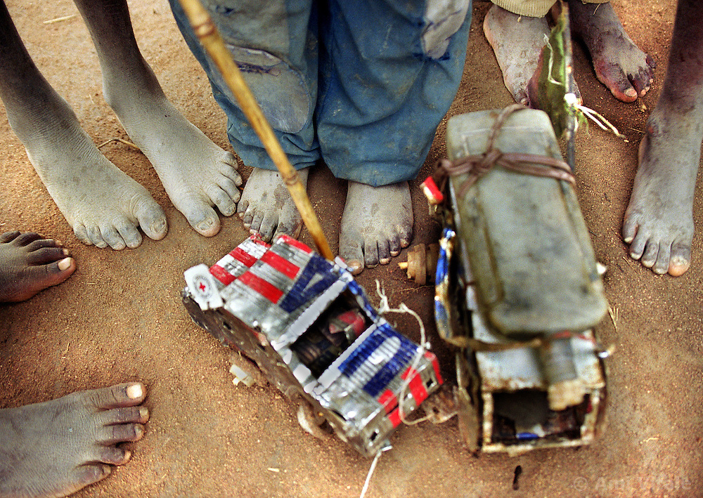 Displaced Angolan children create toys out of cans that brought food distributed by the United States government in a refugee camp in Huambo in March, 2000. Angola's brutal 26 year-civil has displaced around two million people - about a sixth of the population - and 200 die each day according to United Nations estimates. .(Photo by Ami Vitale)