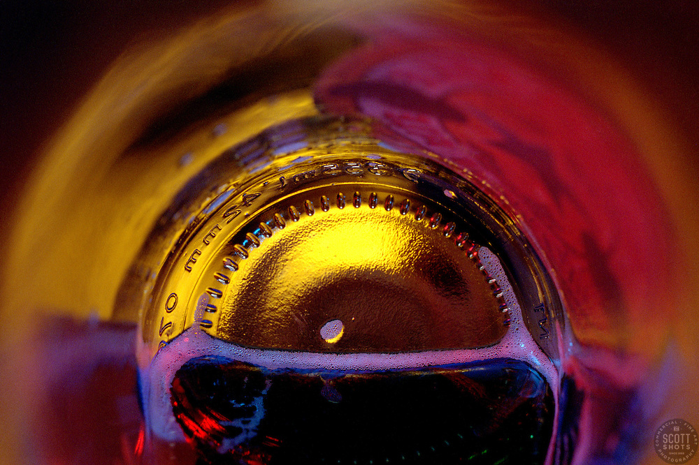 """""""Beauty at the Bottom: Good Night""""- This image is a photograph of a beer bottle shot right down the mouth of the bottle. A television provides the main light source."""