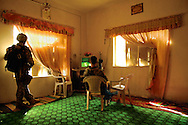 U.S. Army soldier stands guard near a window while his buddy takes a break in front of the television, which is playing Iraqi cartoons, during a raid in Baqubah, Iraq, on April 2, 2007.