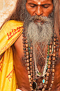 Portait of a holy man sitting in meditation along the Ganges River in the holy city of Varanasi, India.