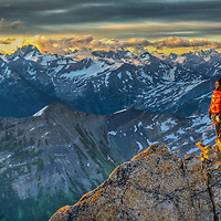 Alex Pedneault watches sunrise from the summit of East Post Spire, Bugaboo Provincial Park, British Columbia Canada.
