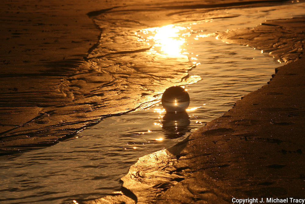 A crystal ball sitting in the runoff and surf of a Jekyll Island beach in the golden sunlight of a sunrise, sunset