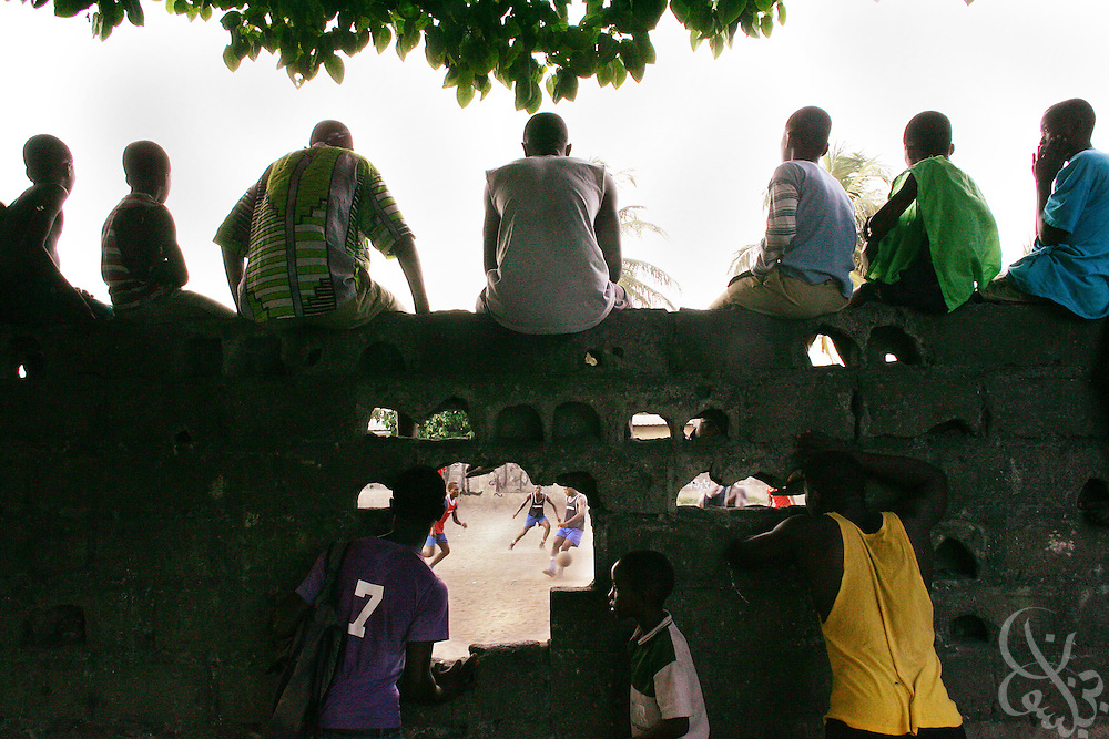 "Supporters watch through a hole in a wall as the ""Almighties of Koomassi"" academy football club practices in the Koomassi neighborhood of Abidjan, Ivory Coast February 17, 2006.  Trying to mimic the successes of ASEC academy, more than 300 rival football academies have been started in Abidjan. Parents hoping of their children will become national team members or pro european league players often become indebted in order to put their children into the copycat academies, which focus on football skills, but do little to educate the young Ivorians who attend them.   ."
