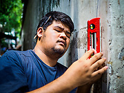 20 MAY 2017 - BANGKOK, THAILAND: An architectural students measures the old city wall in Pom Mahakan. Students of architecture working under the auspices of Vernadoc, an organization that documents historic structures and communities in Thailand, are documenting the historic homes in Pom Mahakan. Bangkok city officials are expected to tear the structure down in coming weeks. The final evictions of the remaining families in Pom Mahakan, a slum community in a 19th century fort in Bangkok, have started. City officials are moving the residents out of the fort. NGOs and historic preservation organizations protested the city's action but city officials did not relent and started evicting the remaining families in early March.        PHOTO BY JACK KURTZ