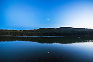 The waxing quarter Moon reflected in the waters of Reesor Lake, Alberta in Cypress Hills Interprovincial Park. Being a quarter Moon it is 90&deg; away from the Sun and in the area of sky with maximum darkening due to natural sky polarization which is visible here as the darker blue area around the Moon and even more so in the water reflection of the sky. A white pelican swims by at left.<br /> <br /> Taken on July 5, 2014. This is with the 14mm Rokinon lens and Canon 6D at ISO800. This is one frame from 400 in a time-lapse. The Moon was in conjunction with Mars (right of Moon) and Spica (left of Moon).
