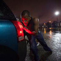 Good Samaritan Elijah Armstrong of Worcester helps push a car out of flood waters on Washington Street and into a nearby Burger King parking lot in Worcester, Massachusetts on October 21, 2016. Flash flooding in the area left many motorists stranded and closed down parts of route I-290.  Photo Copyright Matthew Healey<br /> <br /> (FREELANCE SUBMISSION)