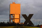 Schacht 1 des Salzstocks in Gorleben im Licht des Sonnenuntergangs. Im Erkundungsbergwerk wird erforscht, ob sich die tiefen geologischen formationen als Endlagerstätte für hochradioaktiven Müll eignen. Im Vordergrund die Konturen eines X, dem Widerstandssymbol gegen die Atomenergienutzung.