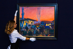 """Sotheby's, London, November 21st 2014.  Sotheby's presents one of its strongest offerings of Russian paintings, icons and artworks as the renowned fine art  auction house celebrates its 25th year in Russia. Pictured: A sotheby's gallery technician straightens Boris Kustodiev's """"Bakhchisarai"""", and oil on canvas painting, described as the most impressive pre-revolutionary painting by Kustodiev to come to light in recent memory. It is expected to fetch between £1.2 and £1.8 million at auction."""