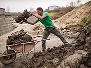09 MARCH 2017 - BAGMATI, NEPAL:  A worker puts clay into a wheelbarrow to take it to workers at a brick factory in Bagmati, near Bhaktapur. There are almost 50 brick factories in the valley near Bagmati. The brick makers are very busy making bricks for the reconstruction of Kathmandu, Bhaktapur and other cities in the Kathmandu valley that were badly damaged by the 2015 Nepal Earthquake. The brick factories have been in the Bagmati area for centuries because the local clay is a popular raw material for the bricks. Most of the workers in the brick factories are migrant workers from southern Nepal.           PHOTO BY JACK KURTZ