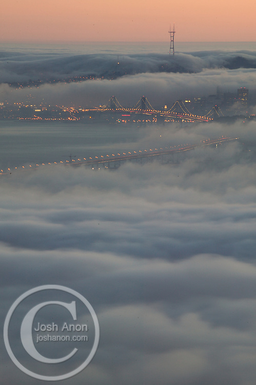 USA, Berkeley, California A fog bank seen from the Berkeley hills rolls into the San Francisco bay, covering the bay bridge. Credit as: © Josh Anon / Jaynes Gallery / DanitaDelimont.com