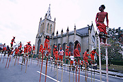 "Trinidad and Tobago ""MOKO JUMBIES: The Dancing Spirits of Trinidad"".(A band of Red Devils, led by Sean Francis, fills the street near Trinity Cathedral, Port of Spain. The band was designed by Laura Anderson Barbata.).A photo essay about a stilt walking school in Cocorite, Trinidad..Dragon Glen de Souza founded the Keylemanjahro School of Art & Culture in 1986. The main purpose of the school is to keep children off the streets and away from drugs..He first taught dances like the Calypso, African dance and the jig with his former partner Cathy Ann Samuel.  Searching for other activities to engage the children in, he rediscovered the art of stilt-walking, a tradition known in West Africa as the Moko Jumbies , protectors of the villages and participants in religious ceremonies. The art was brought to Trinidad by the slave trade and soon forgotten..Today Dragon's school has over 100 members from age 4 and up..His 2 year old son Mutawakkil is probably the youngest Moko Jumbie ever. The stilts are made by Dragon and his students and can be as high as 12-15 feet. The children show their artistic talents mostly at the annual Carnival, which today is unthinkable without the presence of the Moko Jumbies. A band can have up to 80 children on stilts and they have won many of the prestigious prizes and trophies that are awarded by the National Carnival Commission. Designers like  Peter Minshall , Brian Mac Farlane and Laura Anderson Barbata create dazzling costumes for the school which are admired by thousands of  spectators. Besides stilt-walking the children learn the limbo dance, drumming, fire blowing and how to ride  unicycles..The school is situated in Cocorite, a suburb of Port of Spain, the capital of Trinidad and Tobago..all images © Stefan Falke"