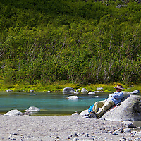 Europe, Norway, Olden. Visitor rests at Briksdal River in Jostedalsbreen National Park.