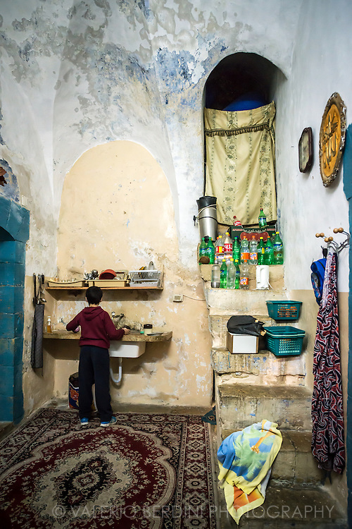 A child helps with the washing-up in what is the entrance and the kitchen of a 800 years old Palestinian home in Hebron Old City.