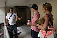 "30/03/2016 - Medellin, Colombia: Carlos Palau, a tourist guide and former policeman, talks with two American tourists, Elizabeth Wilky, 34, and Miguel Nuñez, 34,  inside the Monaco building, the former residence of notorious drug lord, Pablo Escobar. Tours focusing on the life and death of Pablo Escobar are becoming quite popular among international tourists that visit Medellín. In recent times more than 10 tour operators have started to give the tour, helped by the interest generated by Netflix ""Narcos"" series. (Eduardo Leal)"