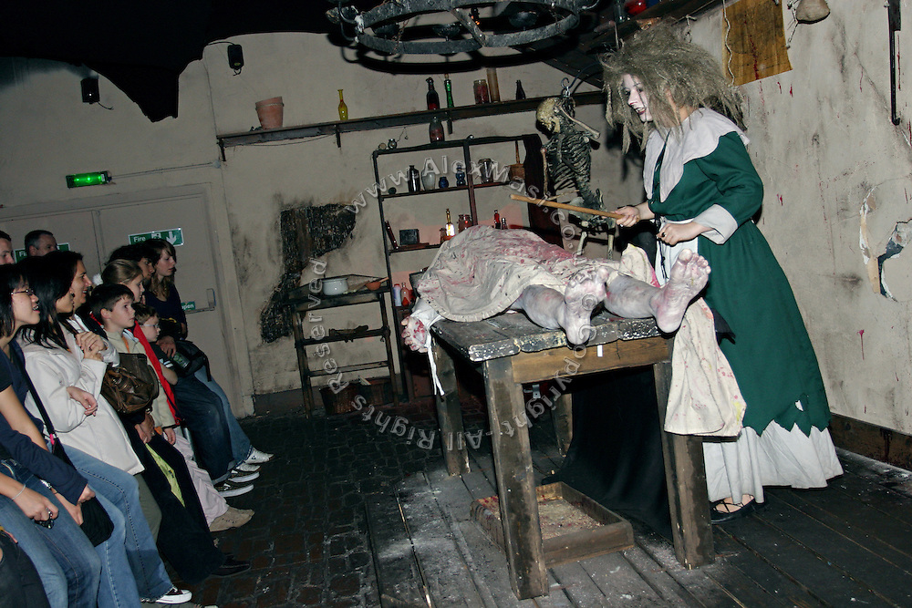 Actress standing in front of a dead body during a play in one of the rooms inside the London Dungeon, England, on Thursday, Oct. 12, 2006. The London Dungeon is a live theatre attraction where visitors are taken by the actors through different areas featuring the darkest parts of British history. Some of the more than 40 exhibits include 'The Great Fire of London', 'Jack the Ripper', 'Judgement Day', 'The Torture Chamber', 'Henry VIII', 'The Tower of London' and 'The French Revolution'. In 2003 a new part opened focused on the Great Plague of 1665.   **Italy Out**..