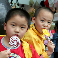 Asia, China; Shanghai. Two Chinese boys enjoy matching lollipops amidst the hustle of Yu Gardens in Shanghai.