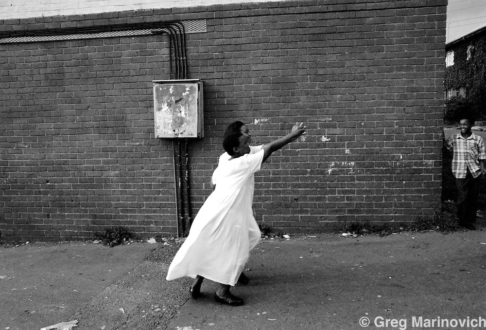 IPMG0343 South Africa, Johannesburg, 1996: Young `coloured' or mixed race girls dance in front of a housing estate in the crime- and drug-plagued Westbury township 1996. The grim low cost flats are home to criminals and law-abiding people.  .Photograph by Greg Marinovich/South Photographs