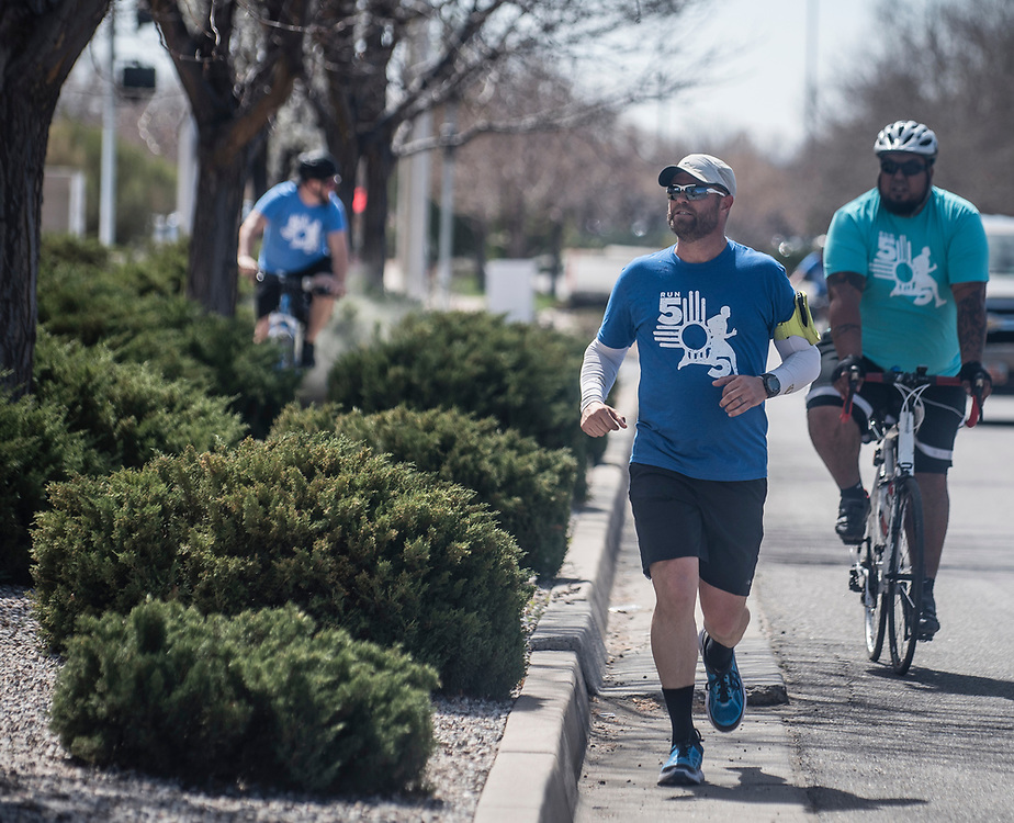 rer031617a/metro/03.16.17/Roberto E. Rosales<br /> Pastor Jason Dickenson(Cq) from Harvest Fellowship will celebrate his 38th birthday by running 38 miles throughout the city to bless the agencies that need so much support, he has several locations along his journey such as APS, CYD, Roadrunner Food Bank, St. Felix food bank, UNM, APD.  Pictured is Dickenson arriving at the Road Runner food bank in the early afternoon followed by a support team Thursday afternoon. <br /> Albuquerque, New Mexico. ( Roberto E. Rosales/Albuquerque Journal.)