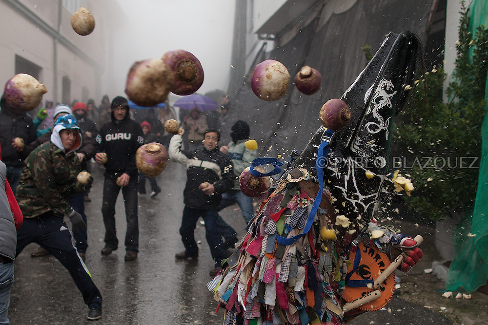 PIORNAL, SPAIN - JANUARY 20: People throw turnips at the Jarramplas as he makes his way through the streets beating his drum during the Jarramplas Festival on January 20, 2013 in Piornal, Spain. The centuries old Jarramplas festival takes place annually every January 19-20 on Saint Sebastian Day. Even though the exact origins of the festival are not known, various theories exist including the mythological punishment of Caco by Hercules, a relation to ceremonies celebrated by the American Indians that were seen by the first conquerors, to a cattle thief ridiculed and expelled by his village neighbours. It is generally believed to symbolize the expulsion of everything bad.  (© Pablo Blazquez)