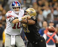 New Orleans Saints Will Smith (91) forces a fumble by New York Giants quarterback Eli Manning (10) at the Superdome in New Orleans, La. on Monday, November 28, 2011. The Giants recovered the ball. New Orleans won 49-24.