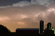 Lightning flashes in the clouds above the barn and silos of a farm in the Town of Wallkill, New York, during a spring thunderstorm.