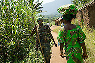 Kikandi Batende, partially obscurred, who is nine moths pregnant, and Mariam Rizik, right, five months pregnant, both 26 years old, walk past a government soldier in their village of Lukweti, Masisi in conflict-ridden North Kivu, Democratic Republic of Congo, July 29, 2014. The village sits at the crossroads of several local rebel groups and has not been treated much better at the hands of the poorly paid government soldiers, the FARDC, who also reportedly raped, looted and attacked villagers.