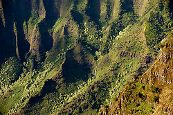 A waterfall cascades down the fluted cliffs in Kalalau Valley at sunset in Na Pali Coast State Wilderness Park. Continious erosion of the volcano that created Kauai has produced the knife-edged cliffs that are the signature of the Na Pali coast. The view is from the Kalalau Lookout in Kokee State Park on the island of Kauai in Hawaii.
