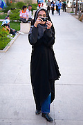 A young woman wearing hijab and jeans takes a photograph with a mobile (cell) phone, Shiraz, Iran
