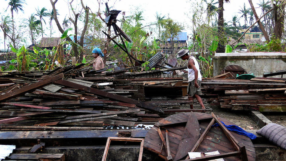 Villagers trying to move away the roof of the monastery that had collapsed during Cyclone Nargis. Around two hundred villagers who were taking refuge in the temple died when it collapsed. All villages surrounding the temple were destroyed in the cyclone; but they still haven't received any aid from their government, and international NGOs have been unable to reach them.