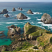 The South Pacific Ocean sweeps across sea stack rocks at Nugget Point, in the Catlins District, South Island, New Zealand.