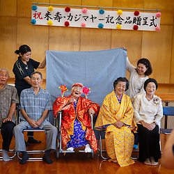 Nintey-seven-year-old Tomi Miyagi sits for her portrait at a celebration in her honor at the town hall in Ogimi, Okinawa.