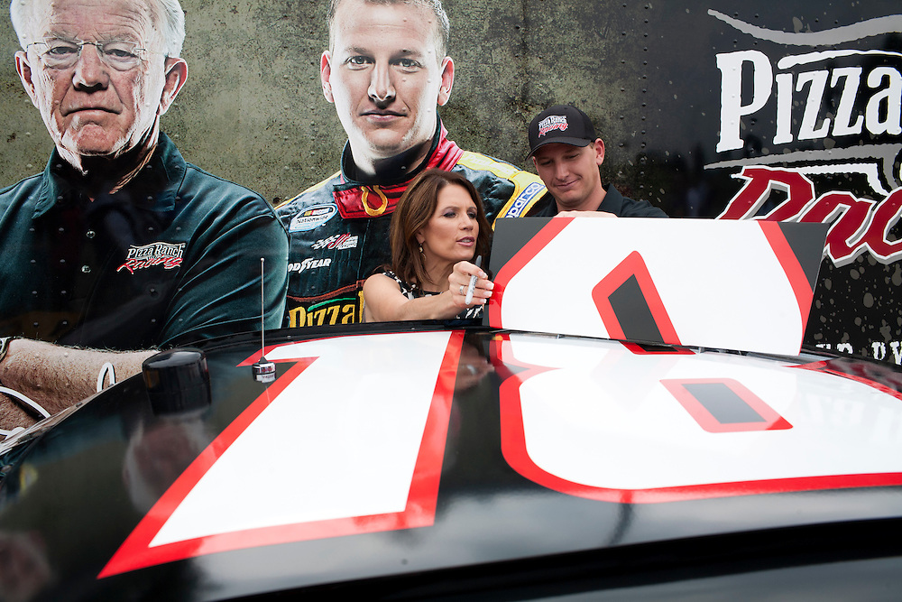 Republican presidential hopeful Michele Bachmann, left, looks at the racecar belonging to driver Michael McDowell of Joe Gibbs Racing, right, after a campaign stop on Friday, August 5, 2011 in Newton, IA.