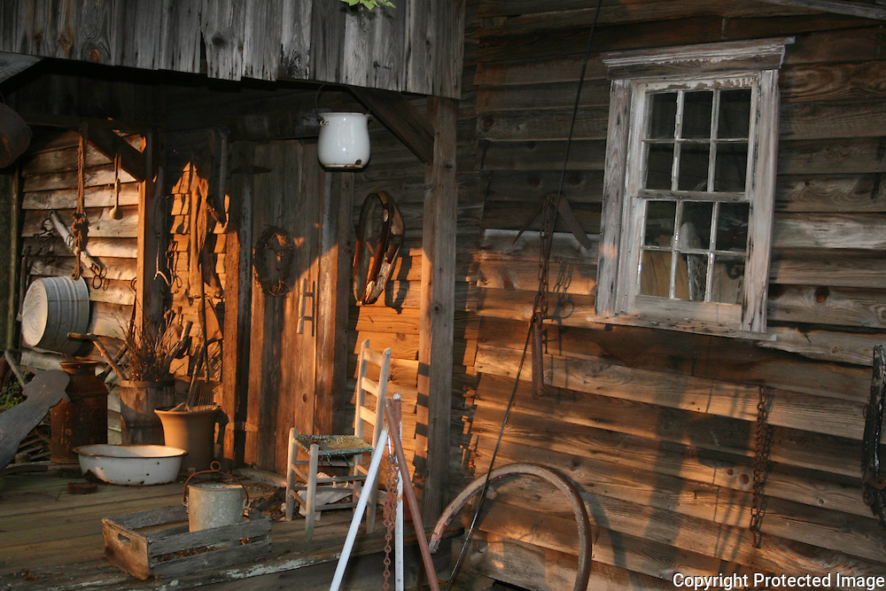 Front doorway to a backwooods, rustic home with antique pots, farm equipment and various other country paraphernalia.